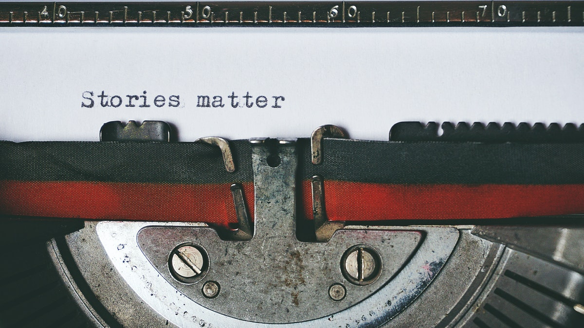 "typewriter with paper that says ""Stories matter"""