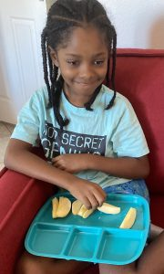 iLEAD Antelope Valley learner Mari eating sliced apples